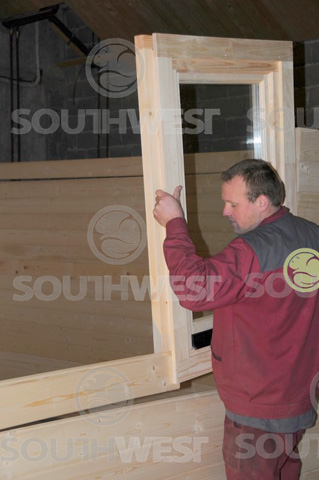 Window being inserted into the log cabin wall
