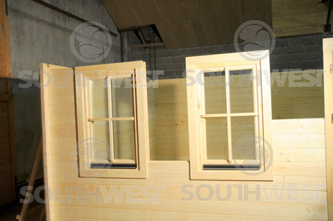 Two windows fitter into log cabin wall